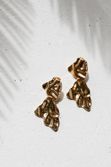 Flat Lay of Gold Hammered Drop Earrings