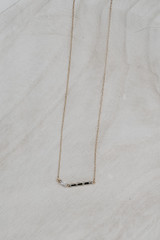 Flat Lay of a Gold Bar Necklace