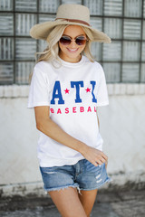 Model wearing the White ATL Baseball Graphic Tee with denim shorts