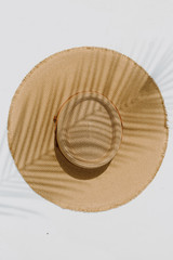 Flat Lay of a Frayed Straw Boater Hat in Dark Natural