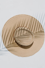 Flat Lay of a Frayed Straw Boater Hat in Natural