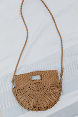 Flat Lay of a Straw Crossbody Bag on a white background