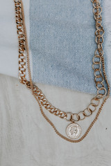 Flat Lay of a Gold Coin Layered Necklace
