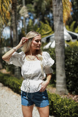 Model wearing a white Smocked Blouse with denim shorts