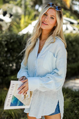 Model wearing an Oversized Linen Blouse with denim shorts