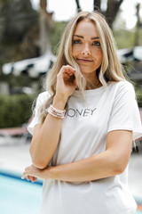 Model wearing the Honey Oversized Graphic Tee with denim shorts