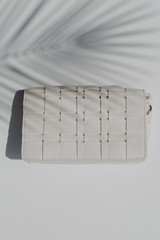 Flat Lay of a Woven Crossbody Bag in White