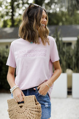 Model wearing the Less Mondays More Sundays Graphic Tee with denim shorts