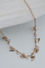 Flat Lay of a Gold Butterfly Charm Necklace