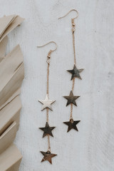 Close Up of Gold Star Drop Earrings