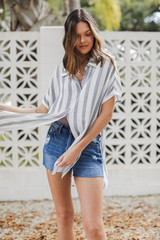 Model wearing a Striped Button-Up Top with denim shorts