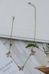 Flat Lay of a Gold Rhinestone Butterfly Necklace