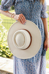 Model holding a Wide Brim Banded Hat in Ivory