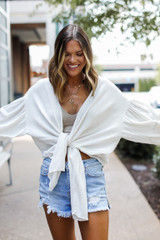 Model wearing a Tie-Front Blouse with denim shorts