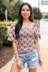 Model wearing a Smocked Floral Blouse with denim shorts