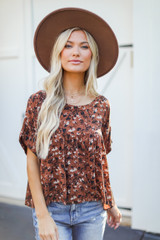 Model wearing a Floral Babydoll Blouse with a wide brim hat