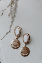 Flat Lay of Gold Smiley Face Drop Earrings