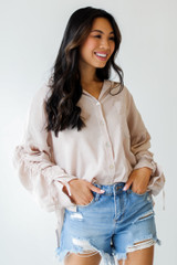 Model wearing a Ruched Sleeve Blouse with denim shorts