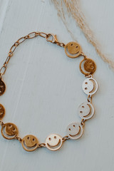 Flat Lay of a Gold Smiley Face Bracelet