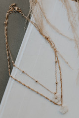 Flat Lay of a Gold Flower Layered Necklace