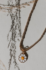 Flat Lay of a Gold Daisy Necklace
