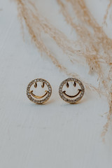 Flat Lay of Gold Rhinestone Smiley Face Stud Earrings