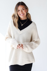 Ivory - Model wearing a Sweater over a black dress
