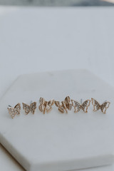 Flat Lay of a Gold Butterfly Stud Earring Set