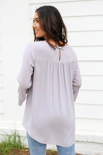 Model wearing Grey Ruffle Sleeve Blouse Back View