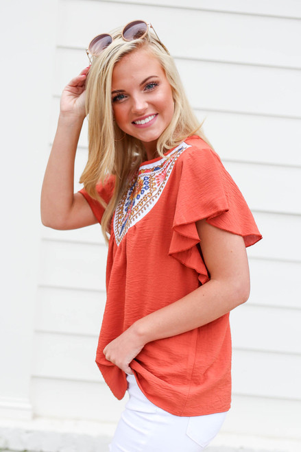 Model wearing Rust Embroidered Ruffle Sleeve Top Side View