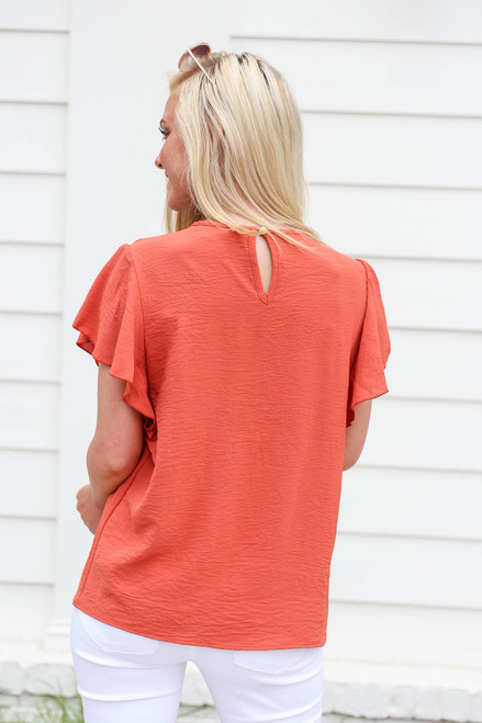 Model wearing Rust Embroidered Ruffle Sleeve Top Back View