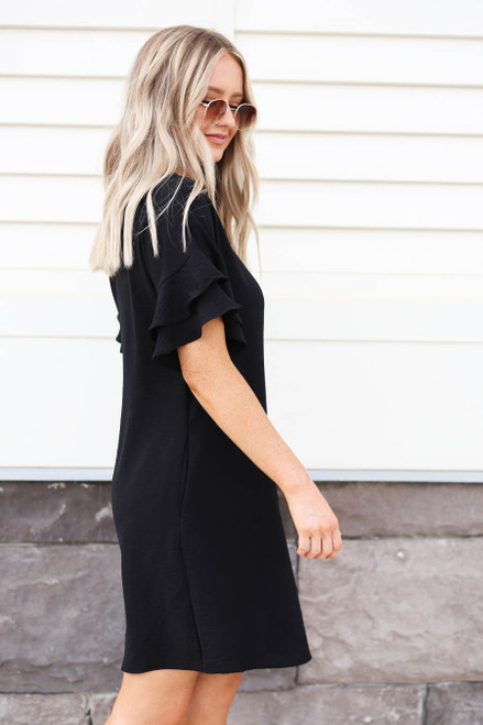 Model wearing Black Ruffle Sleeve Mini Dress Side View
