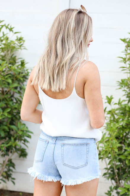 Model wearing Light Wash Distressed Denim Shorts Back View