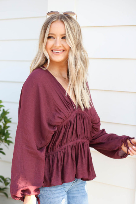 Model wearing Burgundy Long Sleeve Ruched Blouse Side View