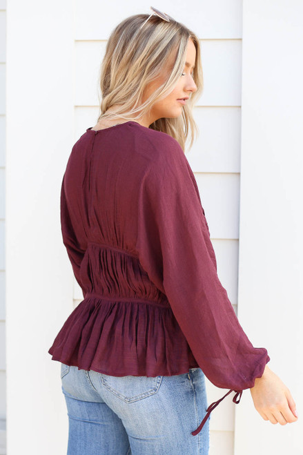 Model wearing Burgundy Long Sleeve Ruched Blouse Back View