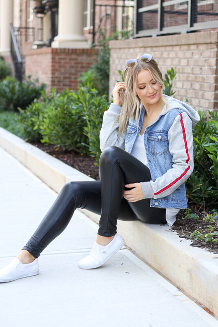 Model wearing Light Wash Denim Vested Hoodie with Side Stripe Sitting Down