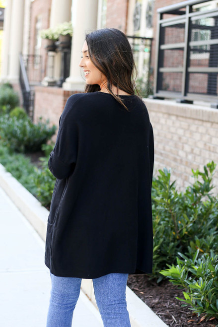 Model wearing Black Oversized Ribbed Sweater Tunic Back View