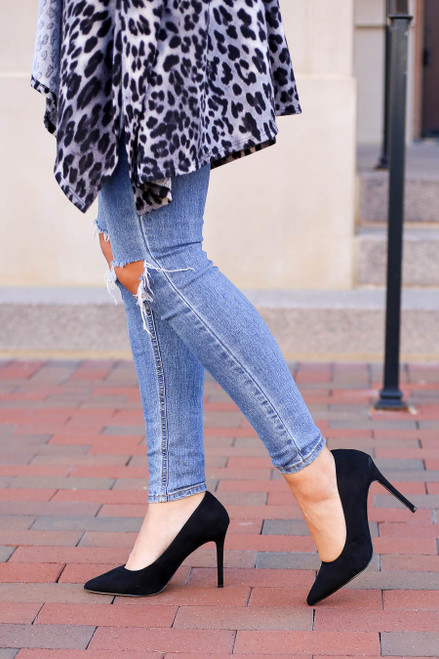 Model wearing black heels paired with jeans ad leopard print kimono
