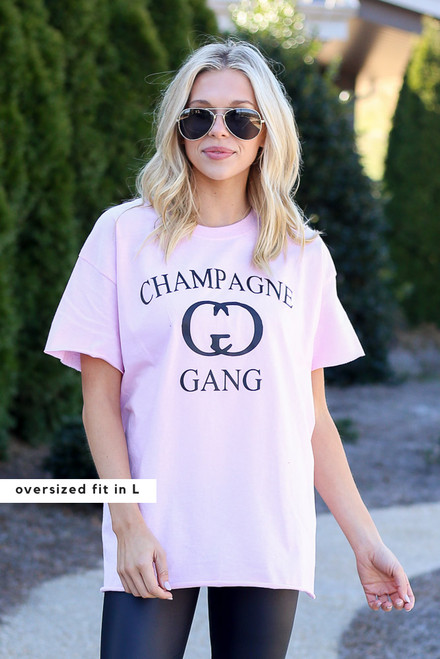 Model wearing the Champagne Gang Graphic Tee from Dress Up in Size Large with faux leather leggings Front View