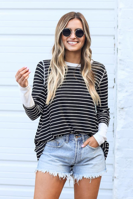 Black - Model wearing the Striped Ribbed Knit Top in Black tucked into jean shorts