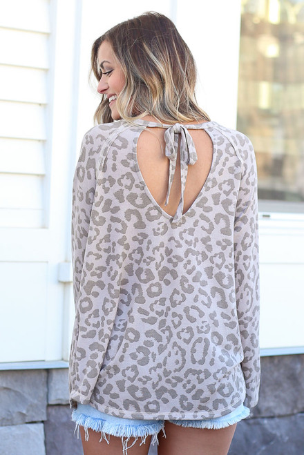Taupe - Model wearing the Taupe Leopard Oversized Tie-Back Top with cut off shorts and sneakers from online dress boutique Back View