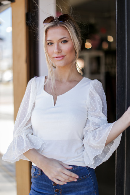 Ivory - Model wearing a Swiss Dot Flounce Sleeve Top