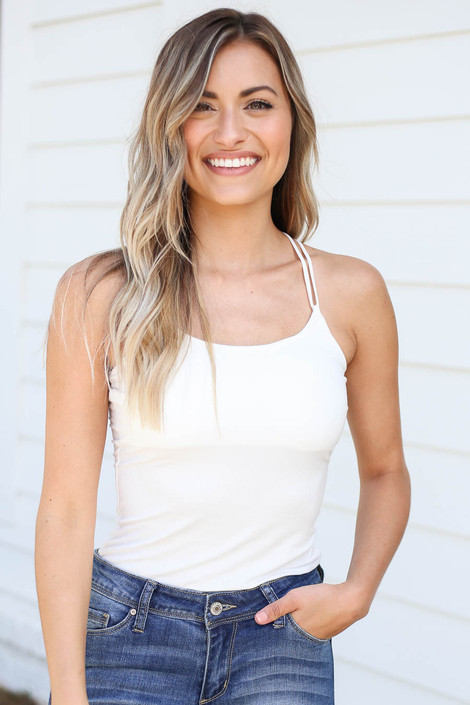Model wearing White Ribbed Bodycon Criss-Cross Back Tank Top Tucked into Jeans
