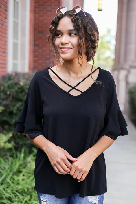 Model wearing Black Criss Cross Ruffle Sleeve Top