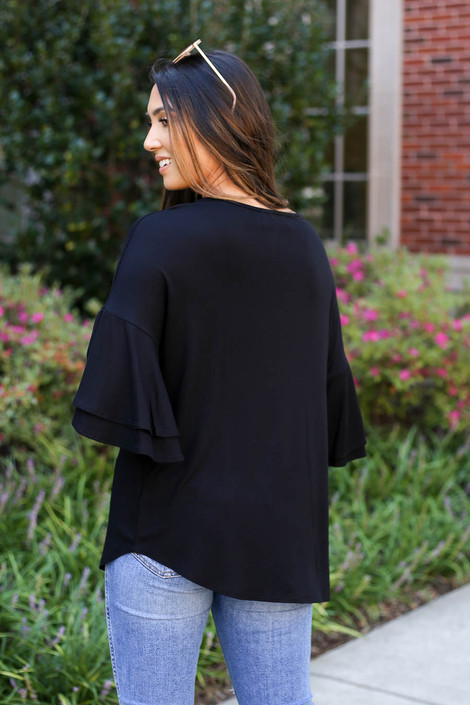 Model wearing Black Criss Cross Ruffle Sleeve Top Back View