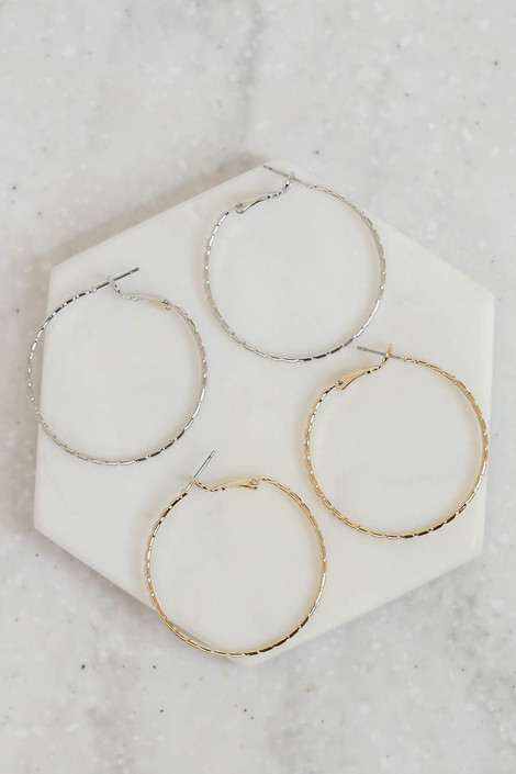 Gold - and Silver Textured Hoop Earrings Flat Lay