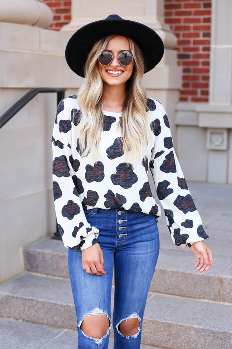 Model wearing Ivory Leopard Print Knit Top Tucked Into Jeans