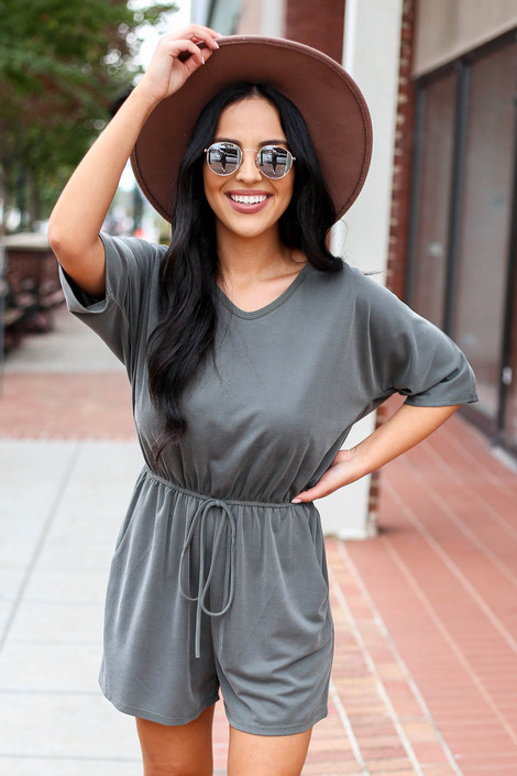 Model is wearing a cheap olive romper with leopard tie back and wide brim hat