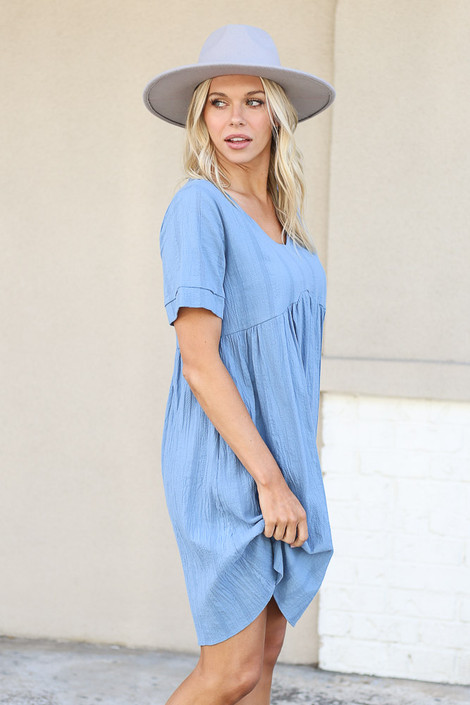 Dress Up Model wearing Blue Textured Short Sleeve Babydoll Dress Side View with wide brim hat