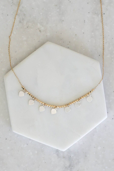 Gold - flat lay of dainty gold necklace with silver charms